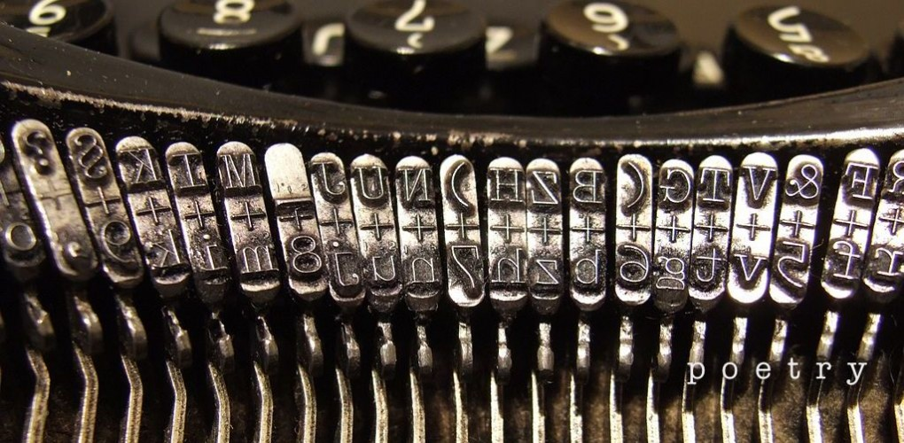 """Close up image of old typewriter strikers, with the word """"poetry"""" superimposed on the bottom right corner."""