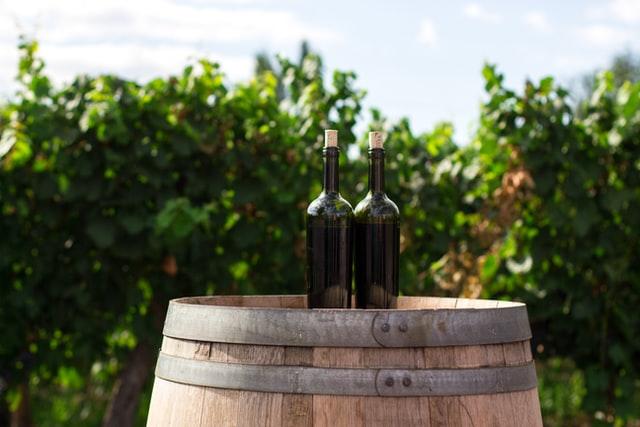 Wine bottles on barrel Photo by Rodrigo Abreu on Unsplash