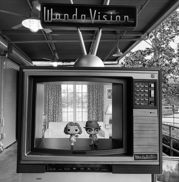 """A black and white image of an old style television, with a pair of dolls in the frame. Above the TV set is a sign that reads """"WandaVision."""""""