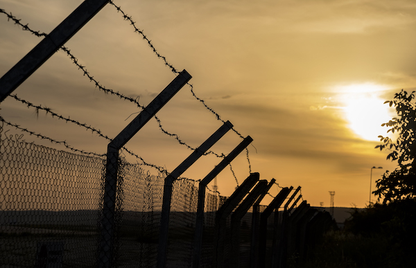 Image of a barbed wire fence at sunset.
