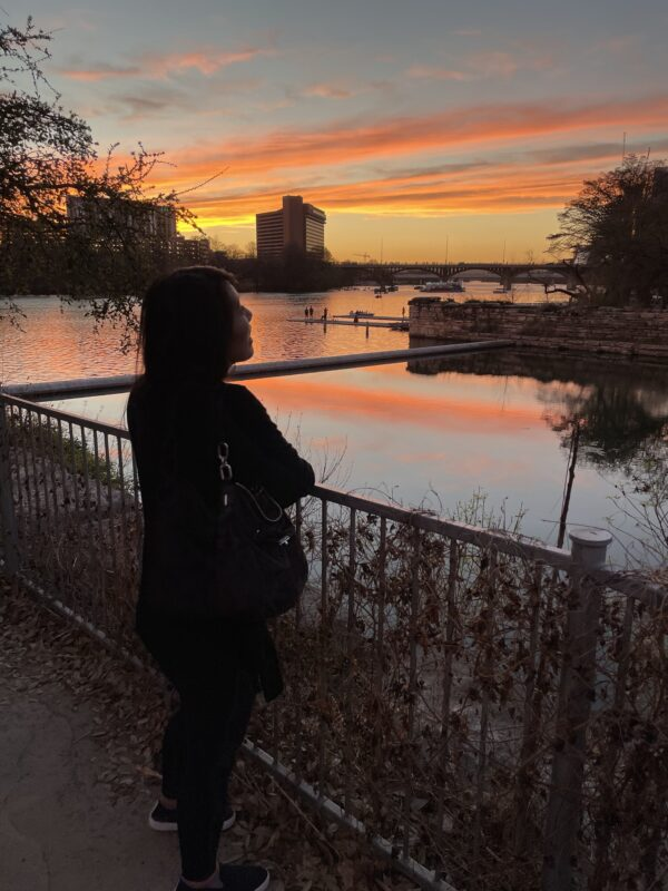 An image of an Asian woman standing at a railing by a body of water, staring right of frame at the orange, gray, yellow sunset.