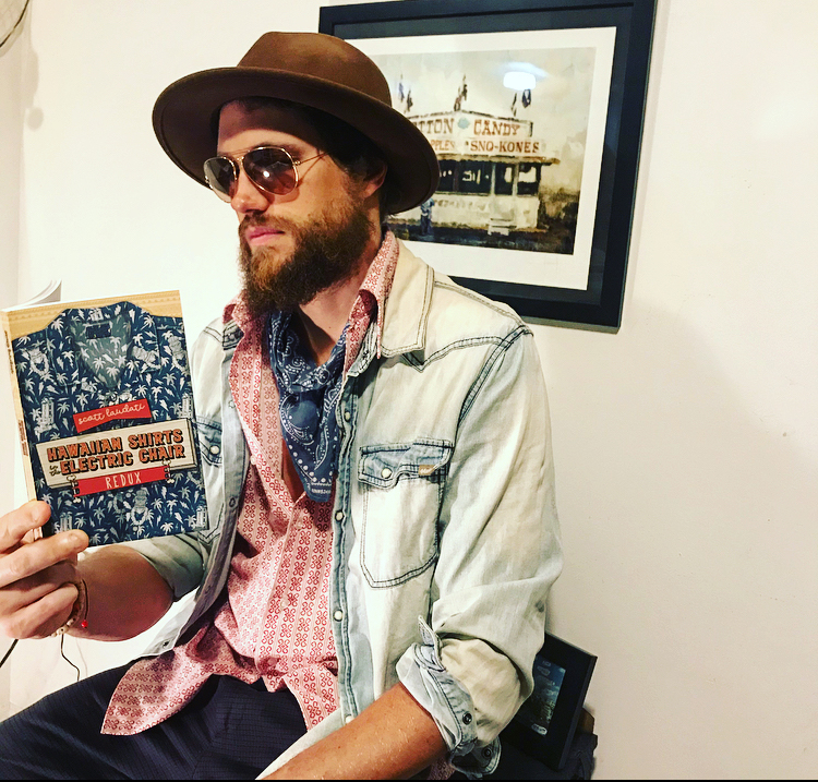 Scott Laudati, looking very cool in his dark shades, brown hat, blue scarf, and pink shirt is reading from his own book, Hawaiian Shirt in the Electric Chair REDUX.