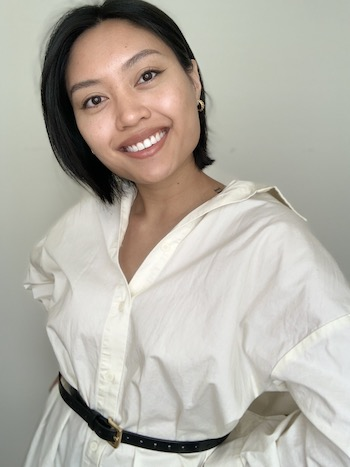 Kendra Quadra smiles, her head slightly tilted to one side, her long white button up shirt tied at the waist with a thin black belt.