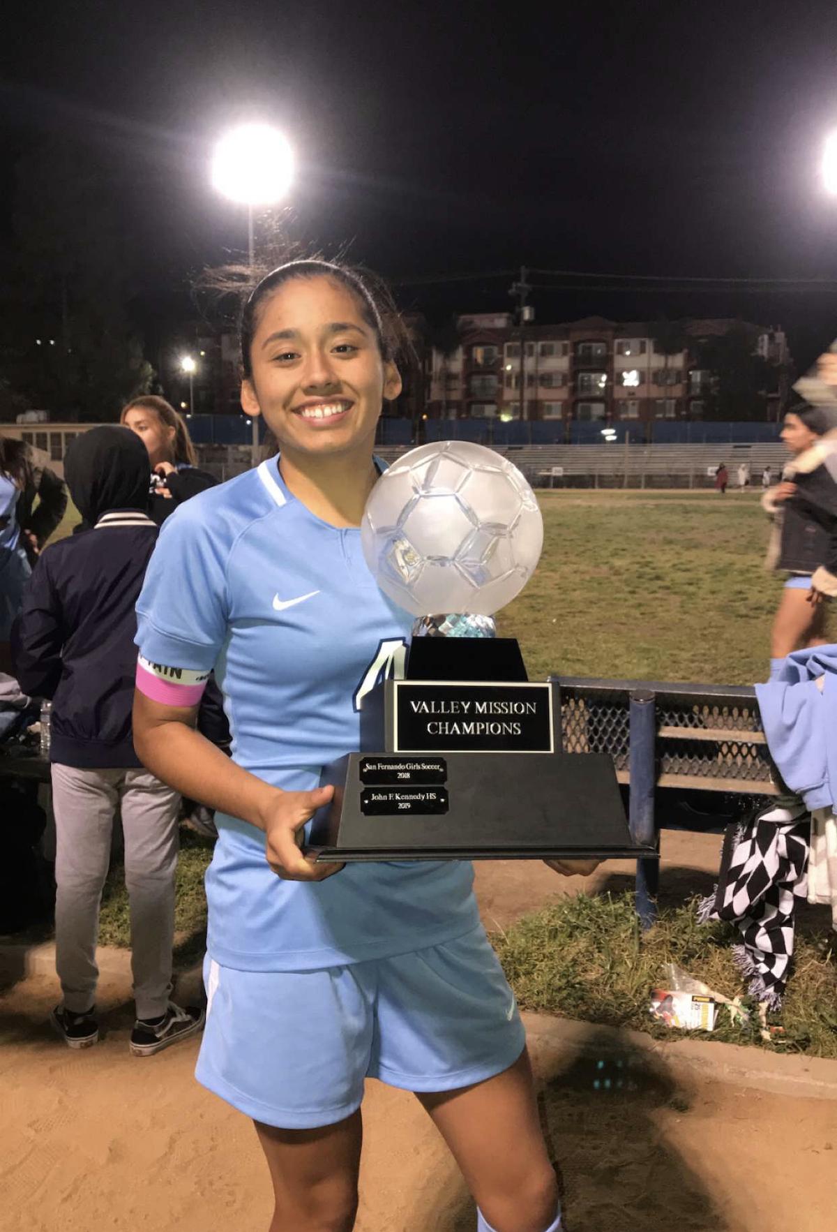Jennifer holding up her MVP trophy