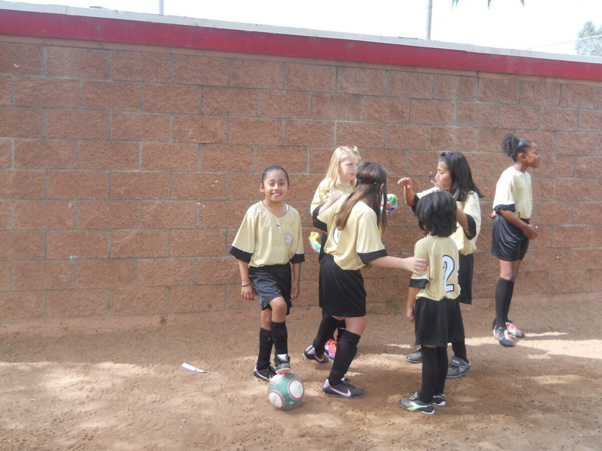 a group of six girls enjoying being around each other in their gold soccer uniforms.