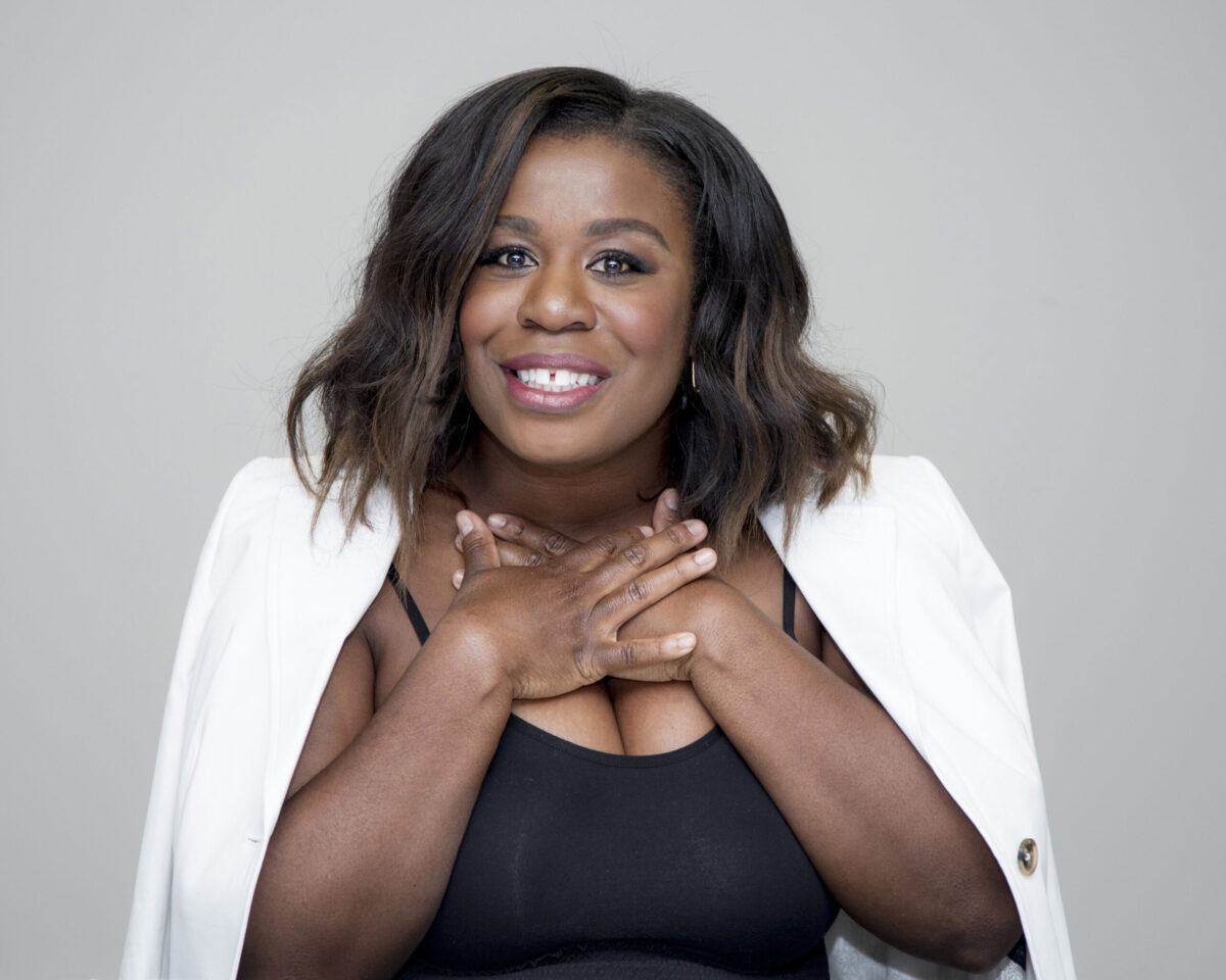 Uzo Aduba with her hands crossed at her chest, a big smile showing her trademark gap. Her hair is straight and a white jacked hangs on her shoulders.